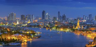 Panorama Views of Bangkok and the Chao Phraya River Wat Arun curve. Against a backdrop of high-rise buildings at dusk.