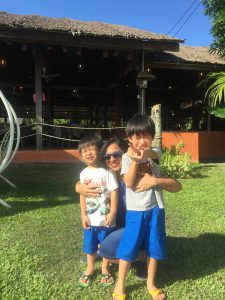 Indian woman posing with two Sabahan children