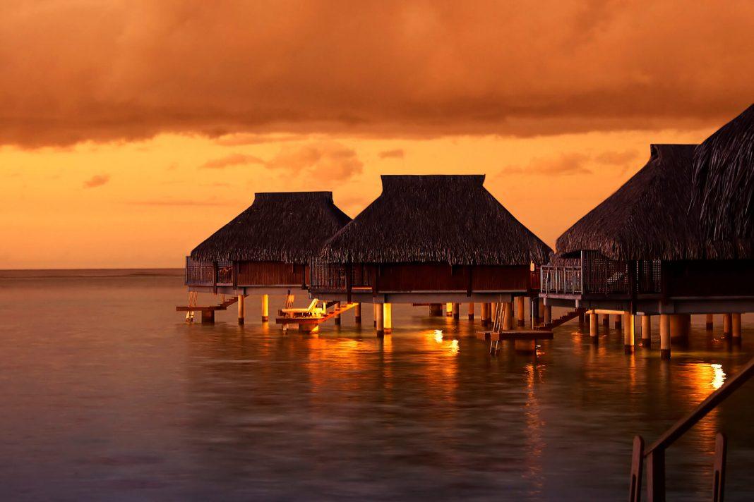 Water houses in the Tahiti sunset - travel to Bora Bora