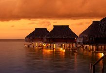 Water houses in the Tahiti sunset - travel to Bora Bora
