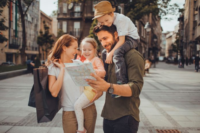 Family with young kids reading a map - travel guide for young parents
