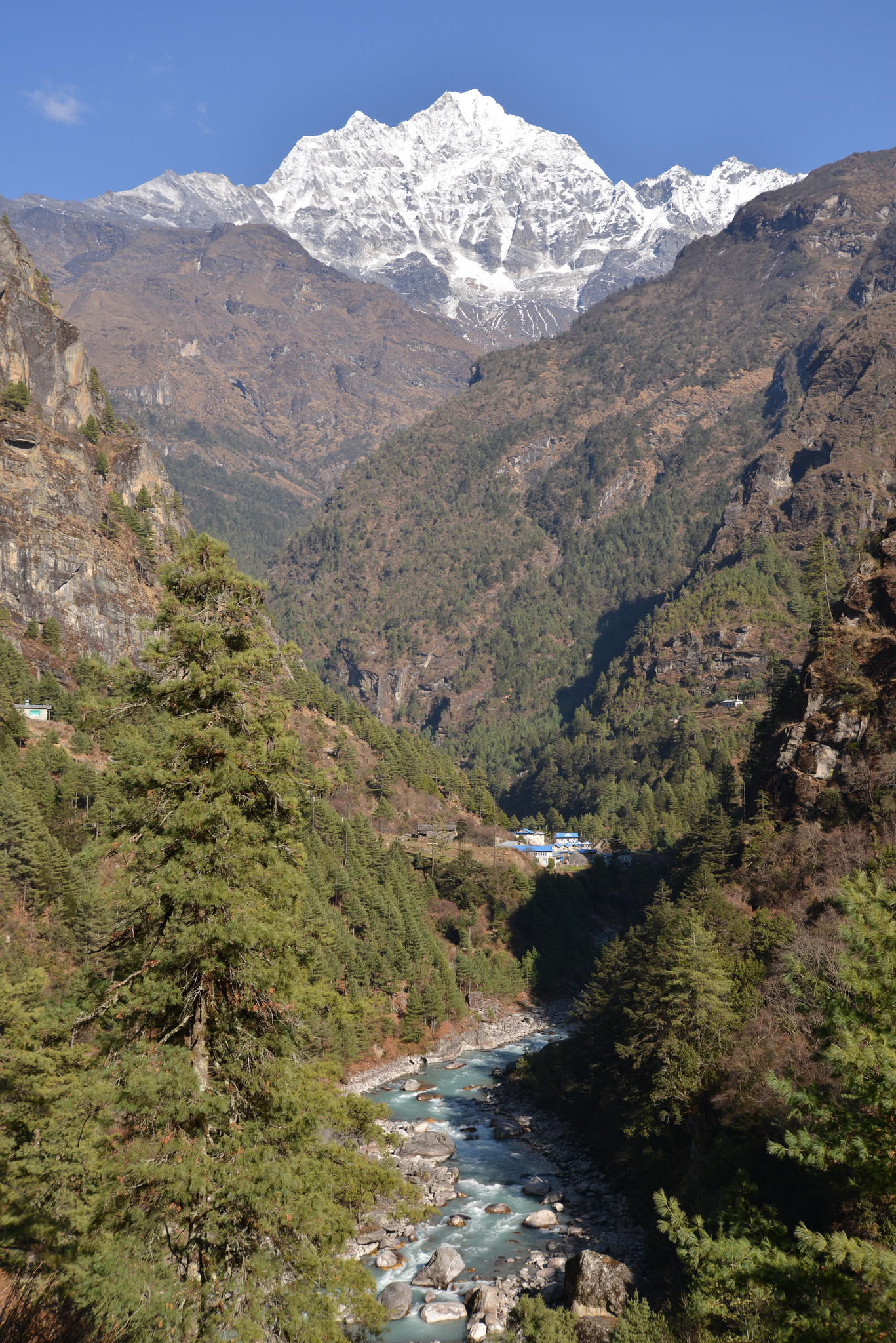 A view of everest in the background, a valley with a gushing stream in the fore ground - everest base camp