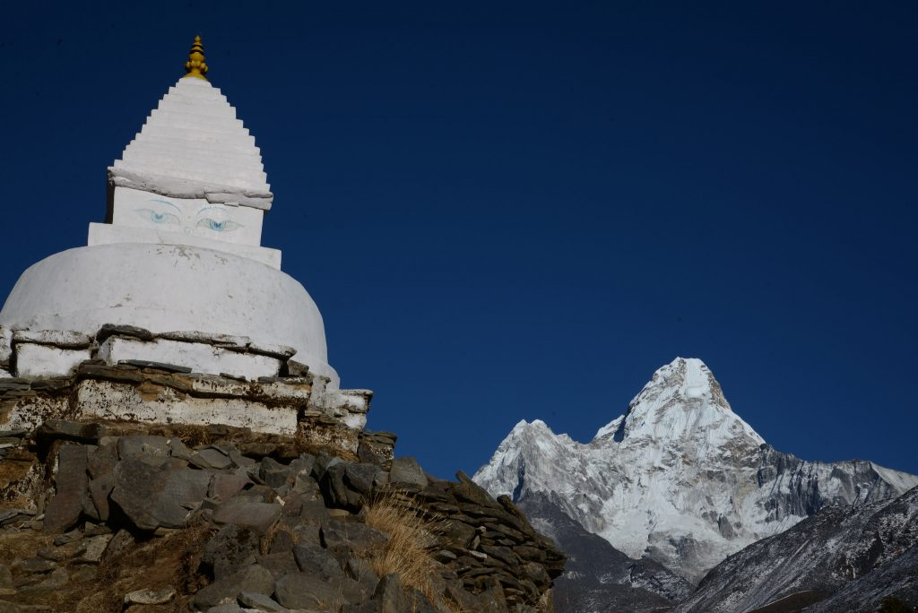 One of the peaks of the Himalayas in the background with a monument in the foreground - everest base camp