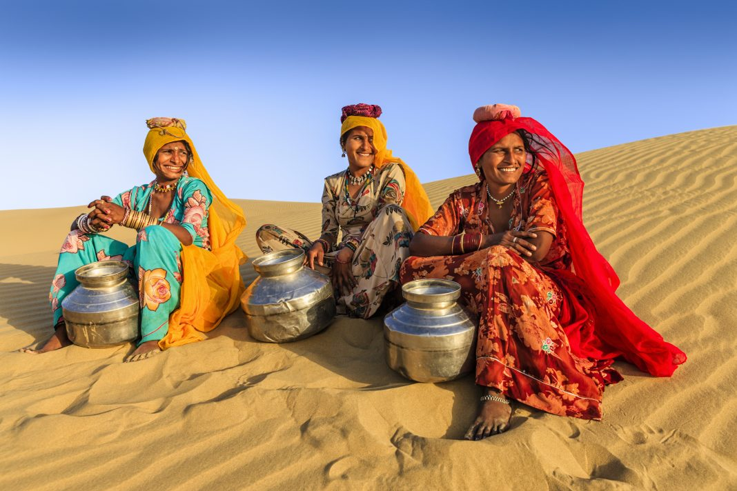 Indian women crossing sand dunes and carrying on their heads water from local well, Thar Desert, Rajasthan, India