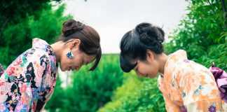 Two Japanese women in traditional kimono bowing