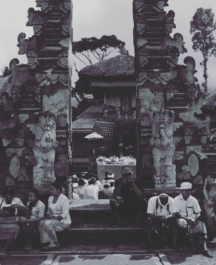People sitting in front of Bali's famous temple