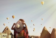 Woman open arms watching like colorful hot air balloons flying over the valley at Cappadocia