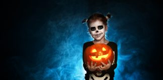 magic skeleton with a pumpkin. baby girl in costume, halloween plans