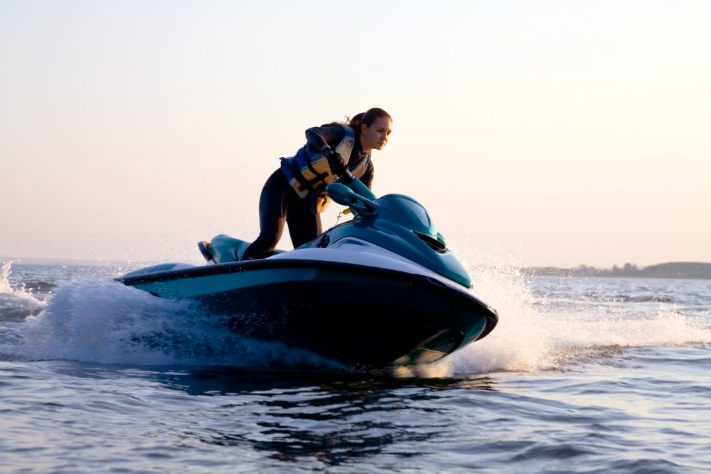Woman on a jet ski in the ocean during the sunset