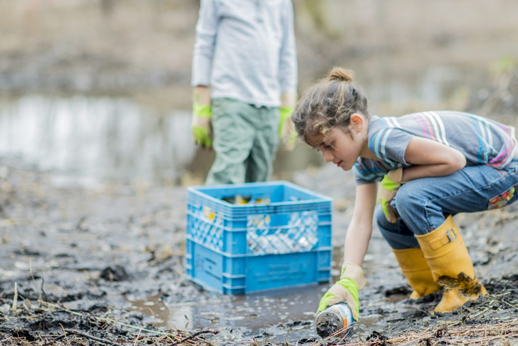 A girl picking up a plastic bottle; plastic pollution while travelling
