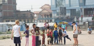 Nepali kids playing with foreign volunteers at one of the earthquake camps in Kathmandu - volunteer tourism