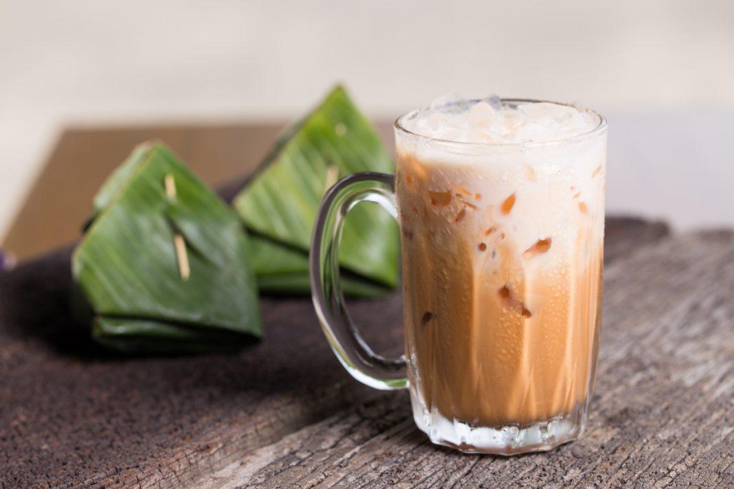 Thai iced tea milk signature local street beverage serve with dessert on wooden table