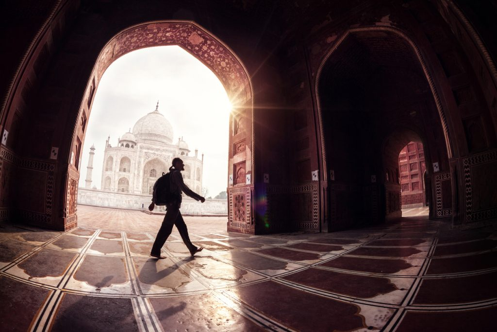 budget solo travel, Tourist with backpack walking in the mosque arch near Taj Mahal in Agra, Uttar Pradesh, India