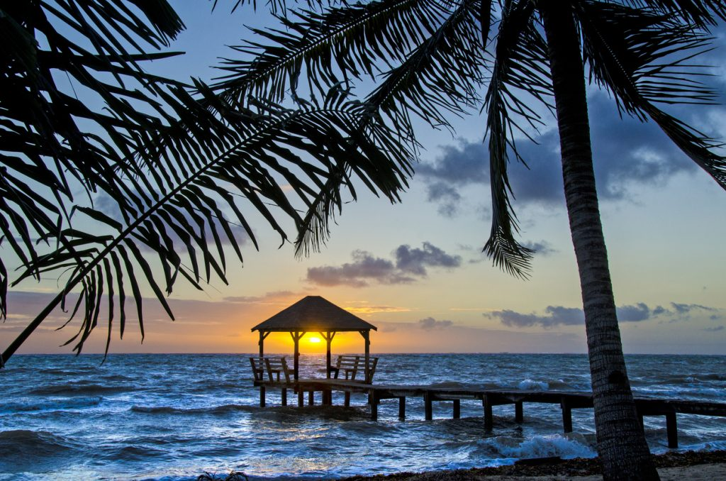 A palapa at sunrise on the end of a pier in Placencia, Belize, best adventure trips for couples
