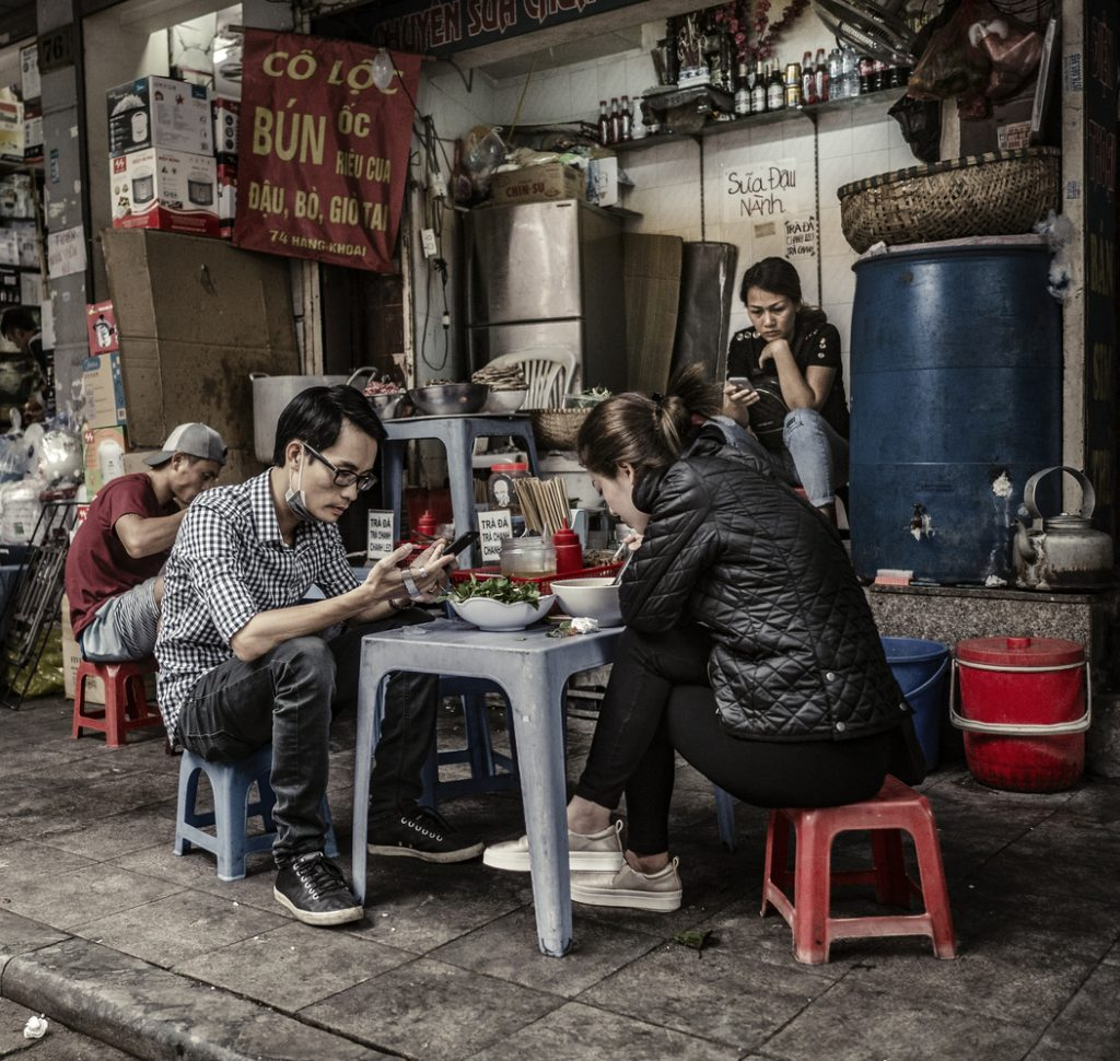 People eating at street food stall in Hanoi old French quarter Vietnam