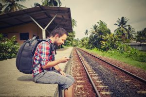 Young solo traveler with mobile phone in the railway