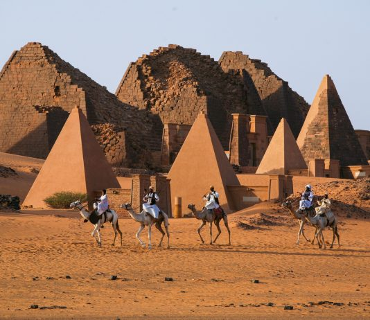 Sudanese bedouins ride camels against the back drop of famous Meroe pyramids of the ancient Nubian city, Sudan