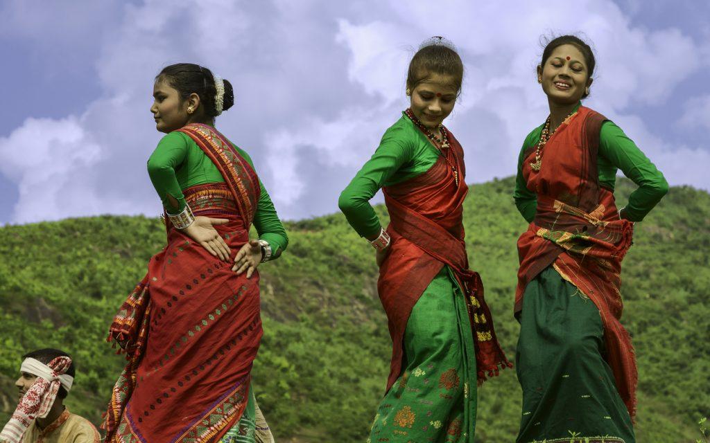 Traditionally dressed local Assamese dancers perform al fresco up in the hills in bright daylight, Guwahati, Assam - Assam Tourism