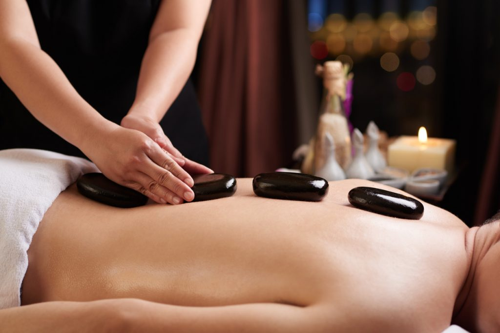 Masseur putting hot stones on the back of a visitor