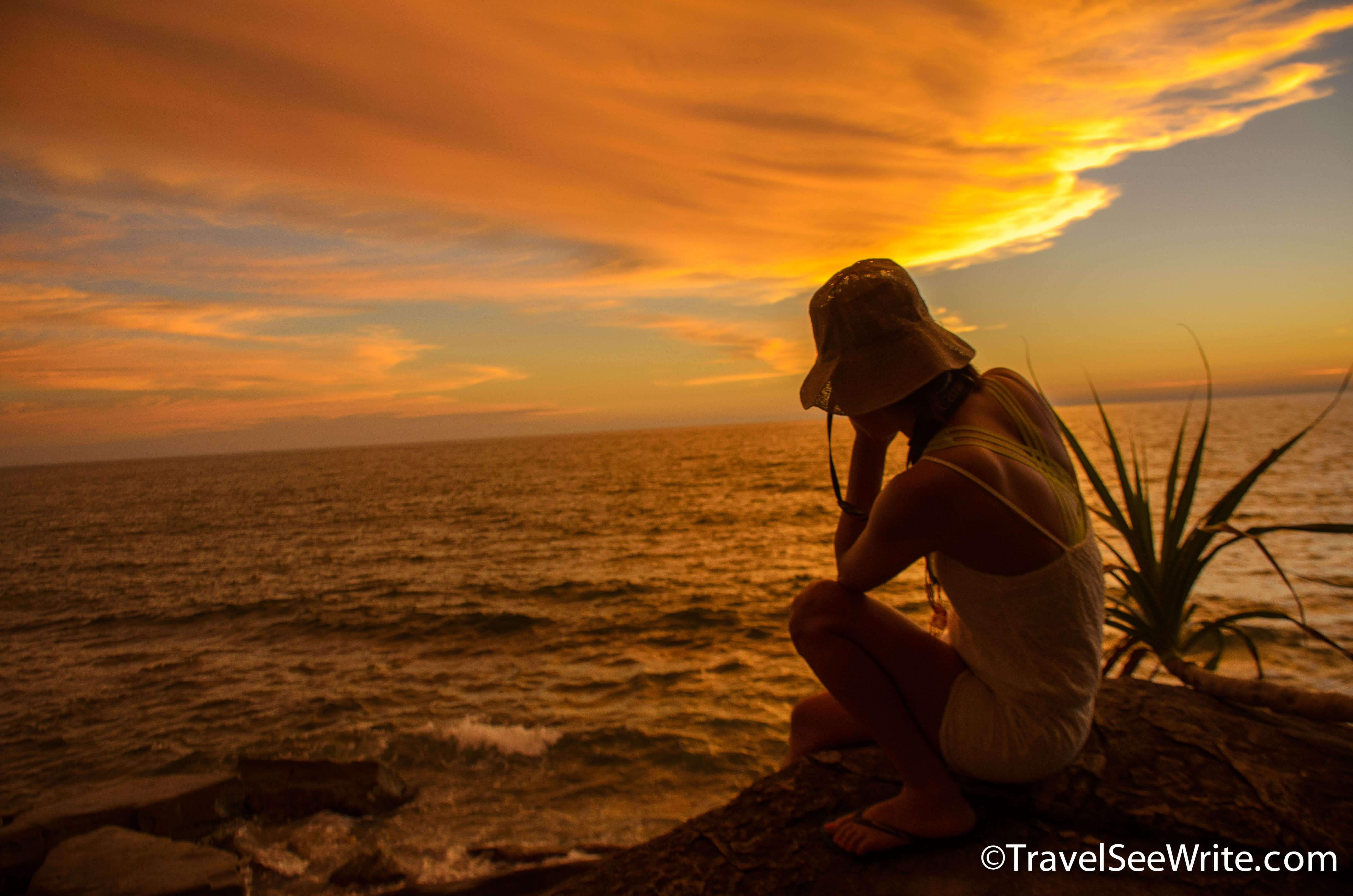 A woman clicking a picture of the stunning sunset - southeast asia travel