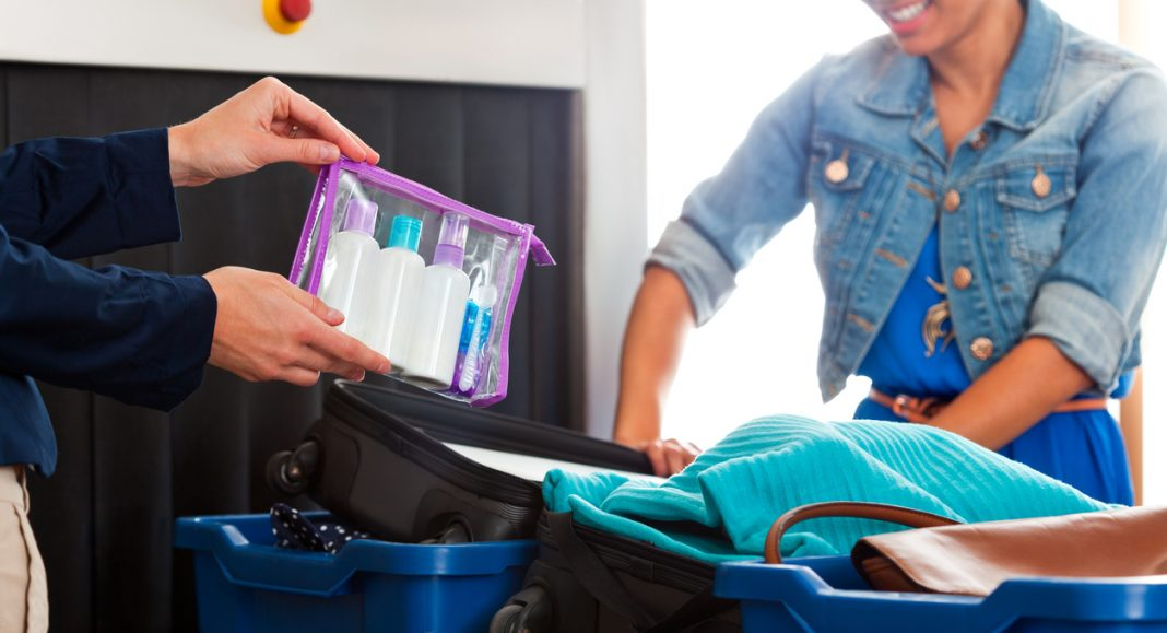 Passenger opening her suitcase at the airport security check, while security staff holding in hands cosmetics permitted in a hand luggage.