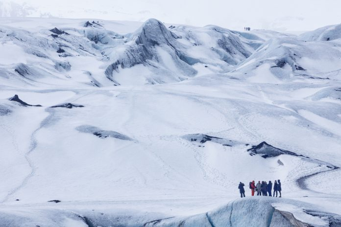 Mýrdalsjökull Glacier, Iceland - March 15, 2014. People preparing to go on a glacier hike at Mýrdalsjökull glacier in Iceland. The glacier is a popular destination for hiking and ice climbing with tourists and locals alike.