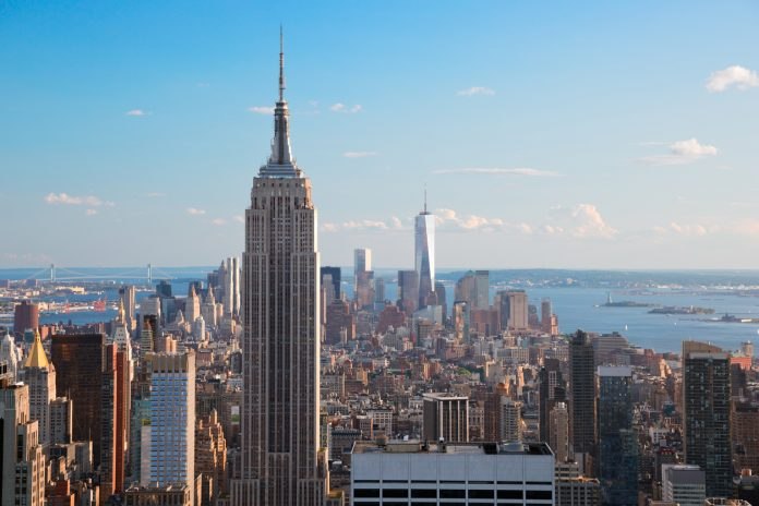Amazing aerial view of Manhattan dominated by Empire State Building. Far is visible the Statue of Liberty.