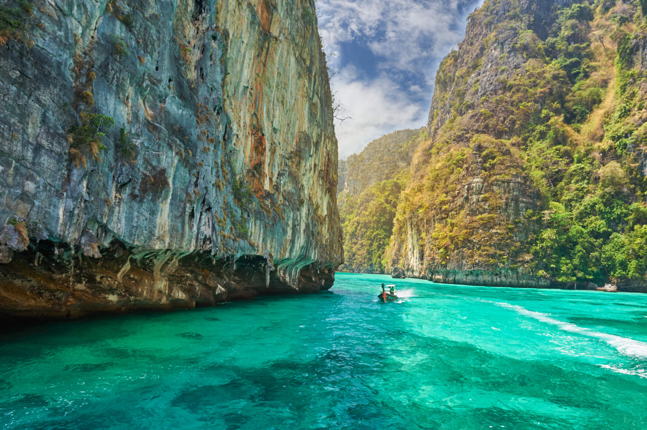A boat cruising on the blue-green waters of phi phi island surrounded by gigantic limestone rocks - places to see in Krabi