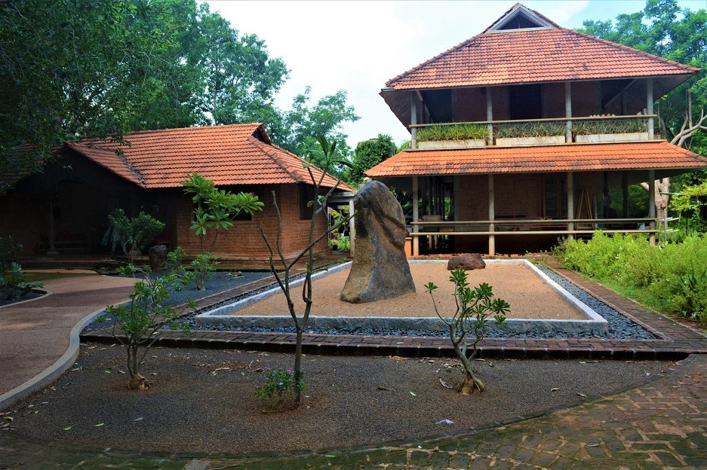 Japanese styled architecture and a standing stone in front of it at AUROVILLE, INDIA