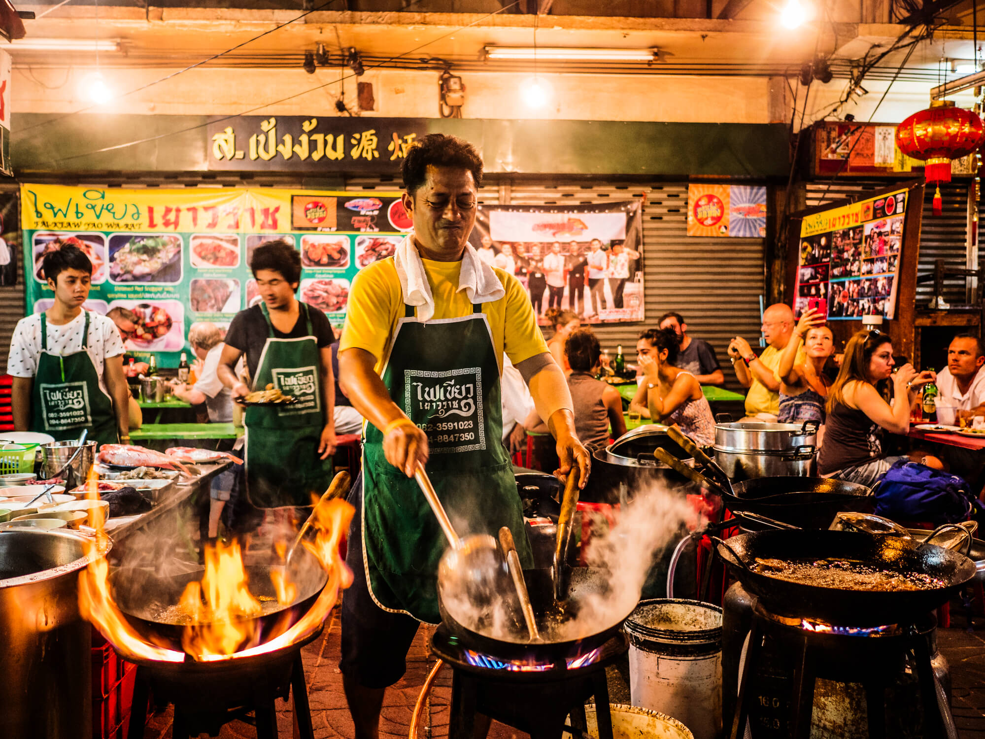 A man sauteing food over a hot wok in Chinatown - best street food in Bangkok