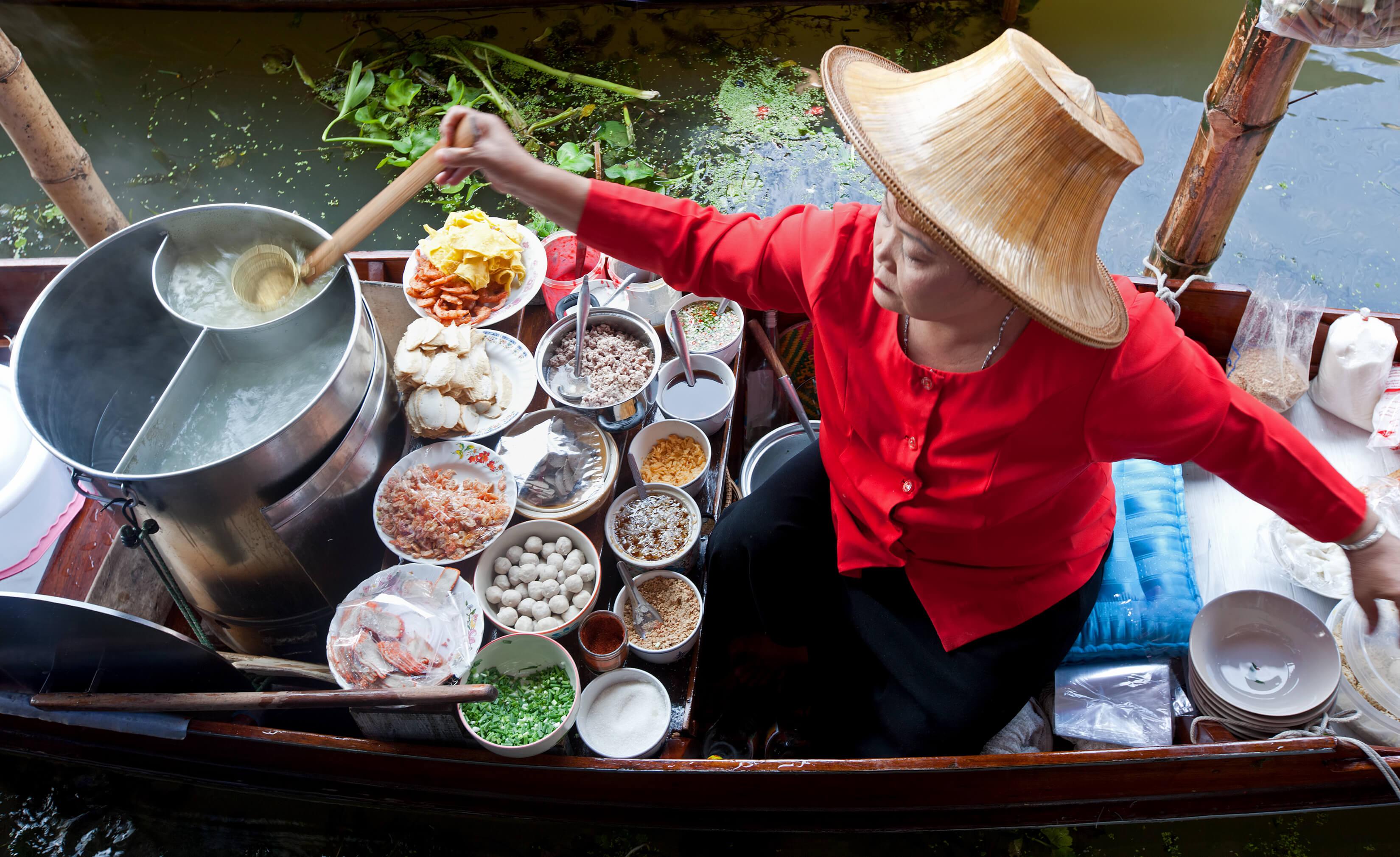 Lady selling food at the floating market in Bangkok - Bangkok street food