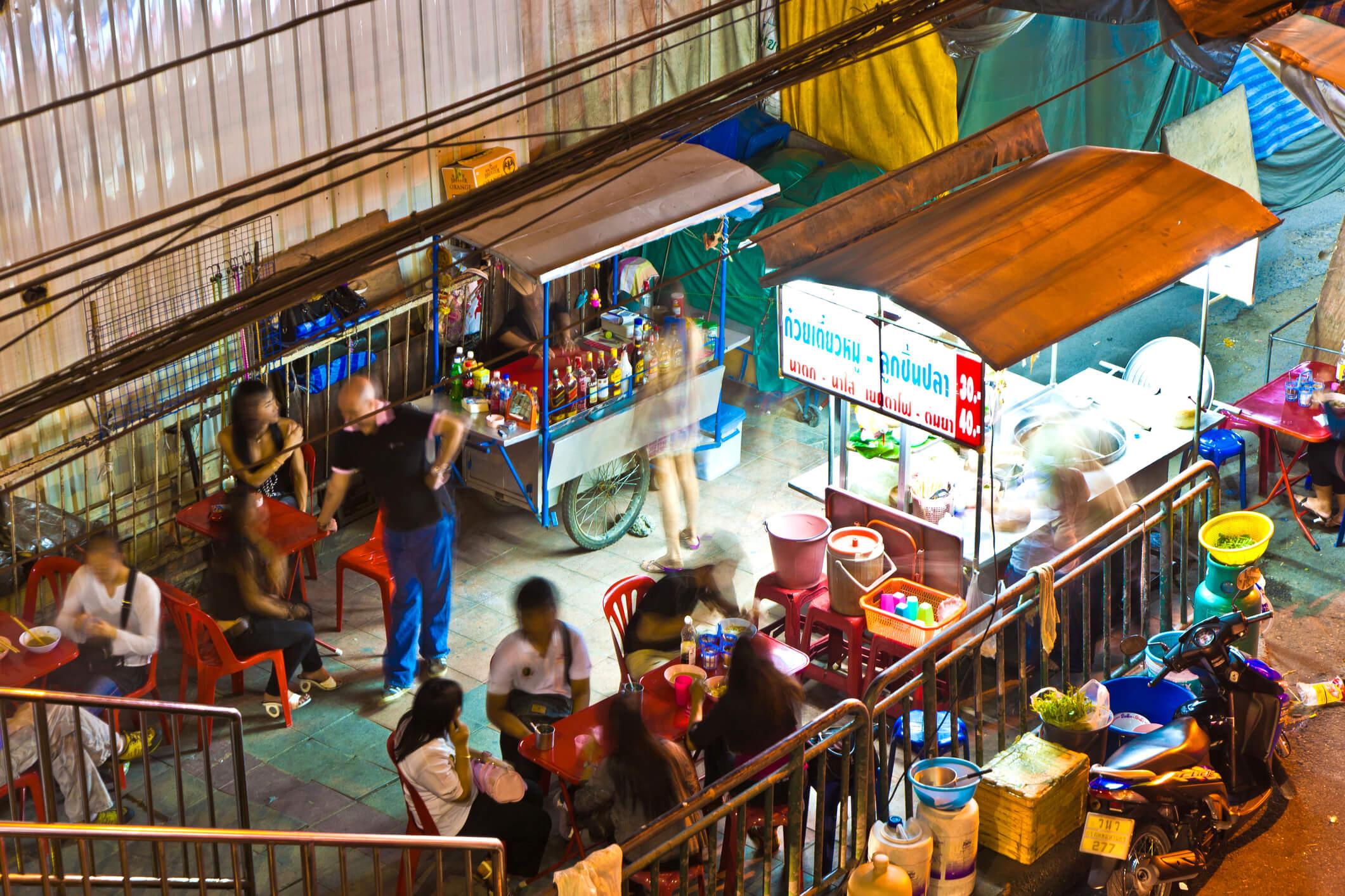 People standing around street food stalls in Sukhumvit - best street food in Bangkok