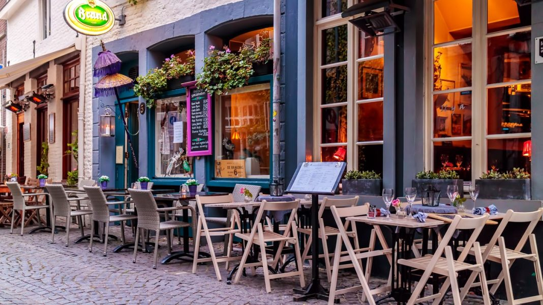 Evening view of empty dinner tables in front of restaurants in Maastricht, The Netherlands