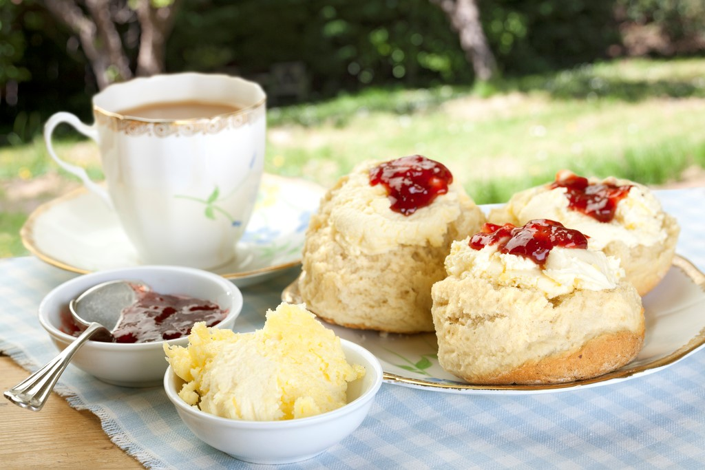 Traditional English Cream Tea overlooking a garden with apple trees.