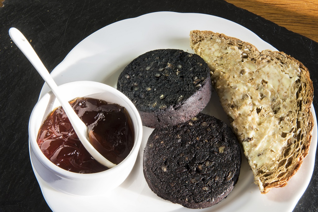 a portion of black pudding on a plate with bread and sauce