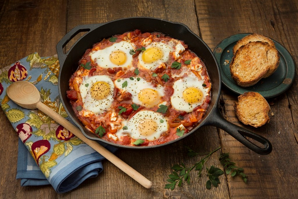 Overhead view of shakshouka on a rustic background.