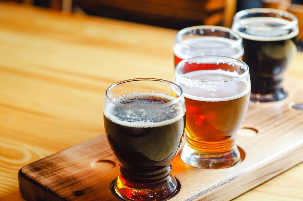 best things to do in Maui, Flight with various types of craft beer in small glasses on a wooden table in a pub