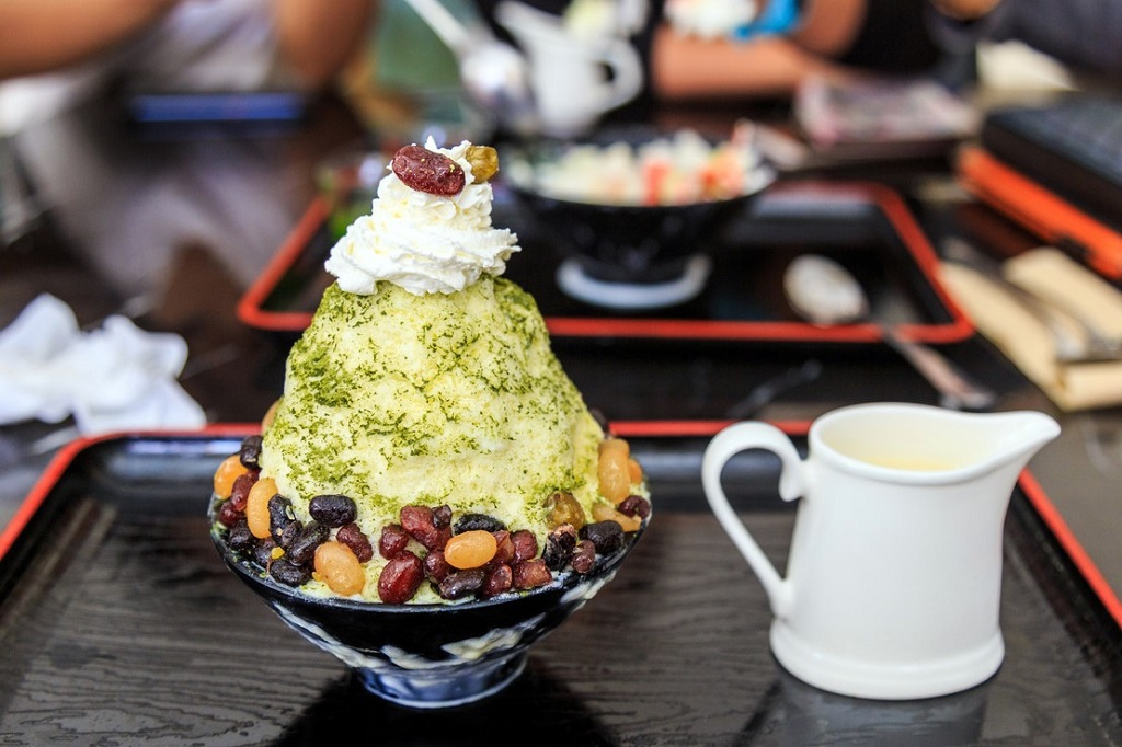 Bingsu green tea with sweet red bean on black cup and black tray with a girl hands background.