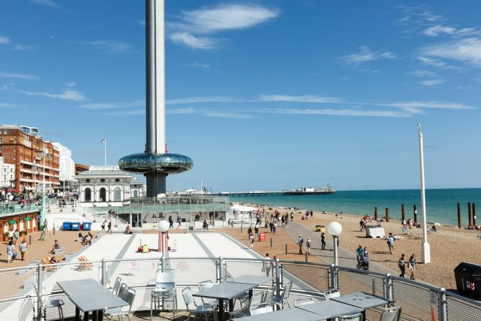 People admire walking on Brighton costline, view of English channel, tower i360