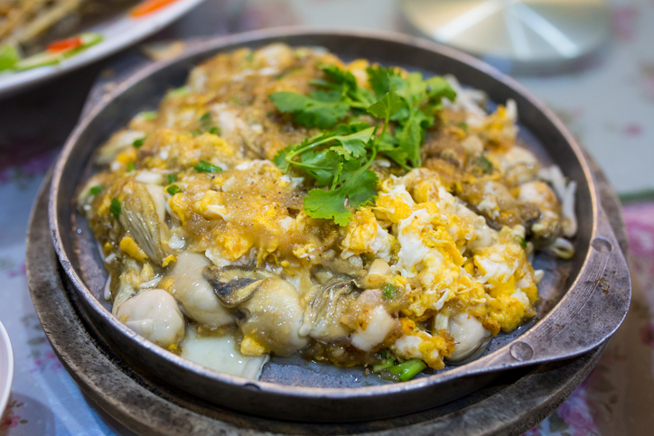 Thai street food, Oysters fried in egg batter on iron pan - best street food in Bangkok