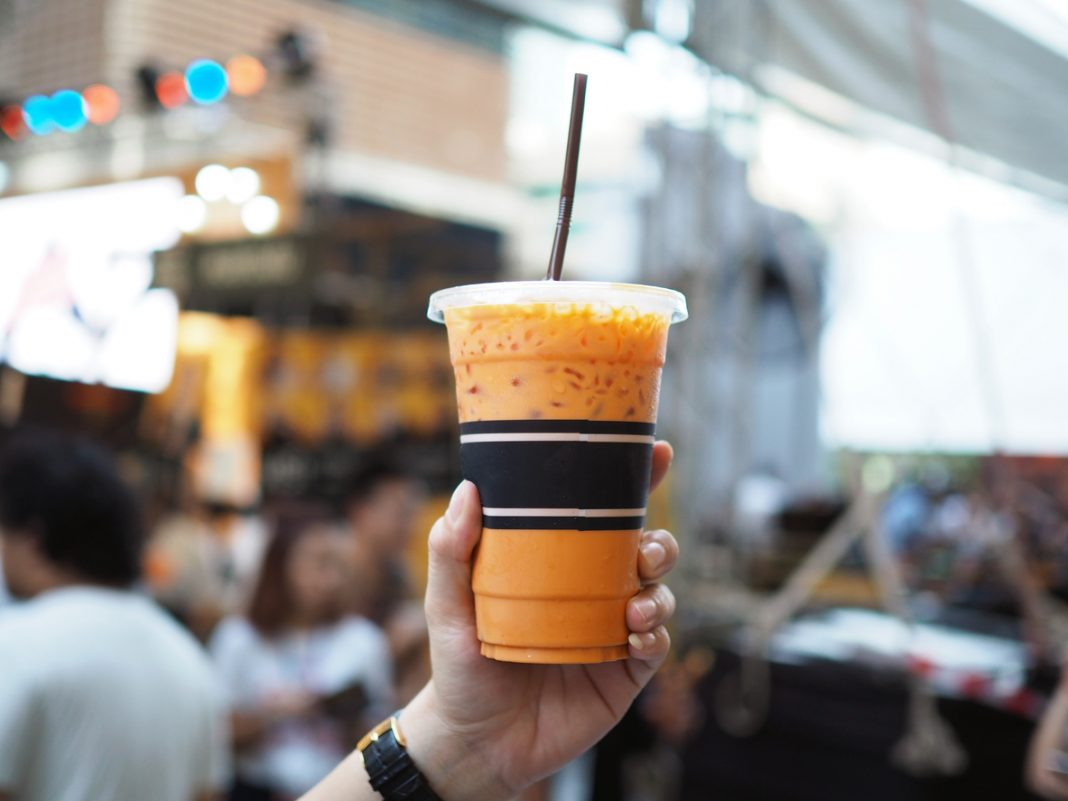 A plastic glass of iced ceylon tea latte - best street food in Bangkok
