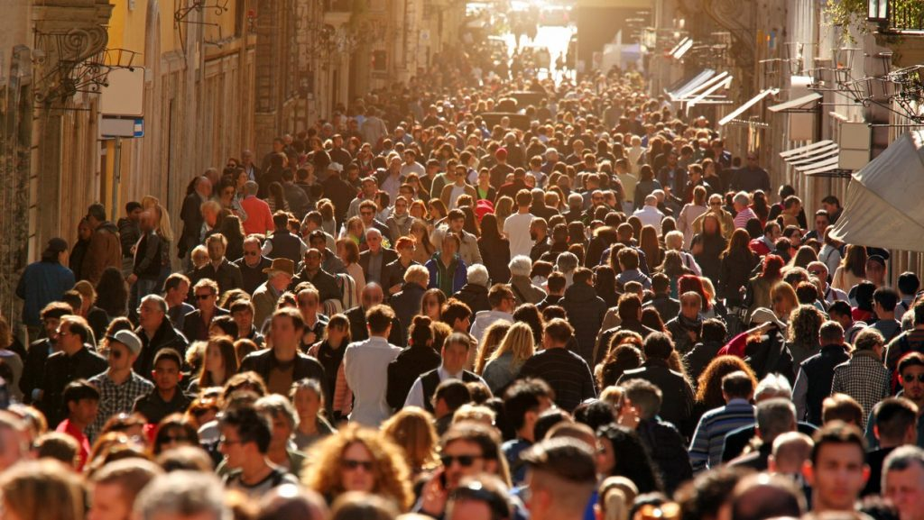 Large group of people crowding Rome's downtown streets in a sunny day.