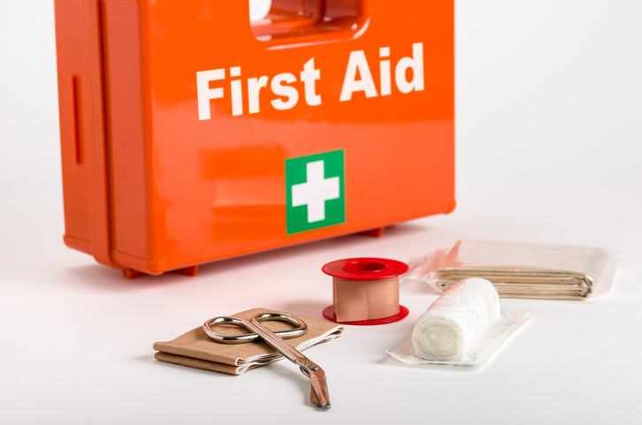 A red first aid box with supplies for dressings in front