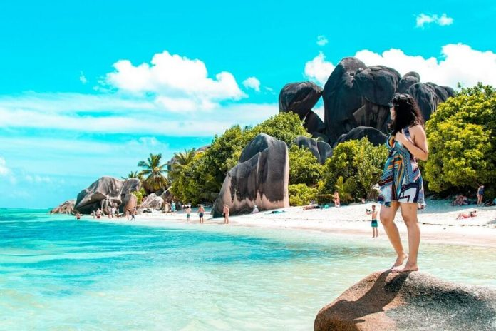 Woman standing on a rock at Anse Source DARgent, Seychelles