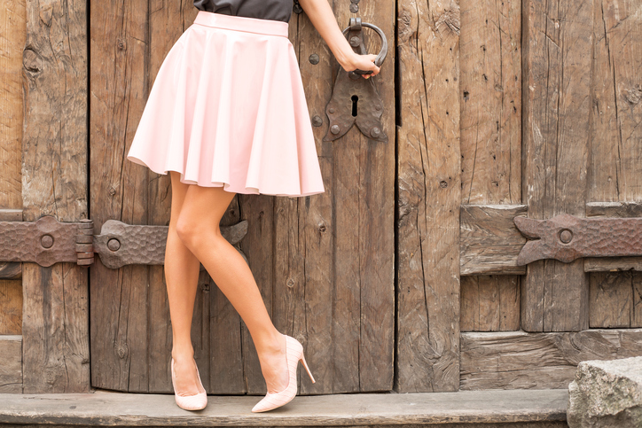Woman wearing nude colored high heel shoes with a-line skirt for travel outfits