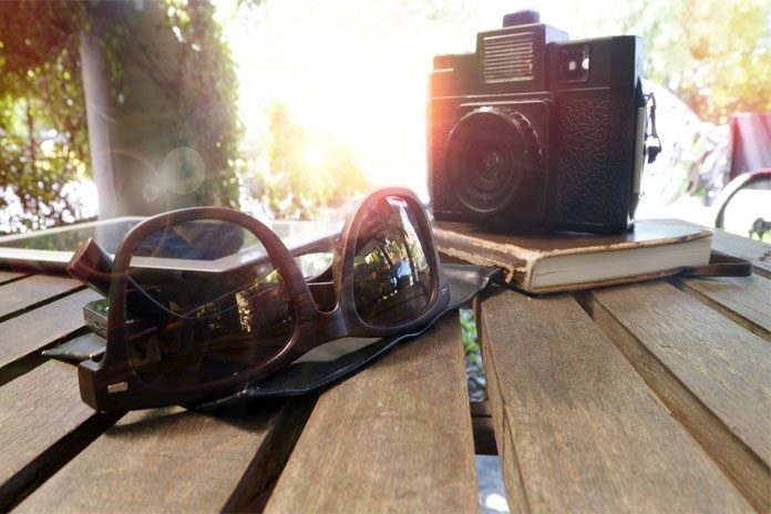 Sunglasses and camera on a table - travelling to Pakistan