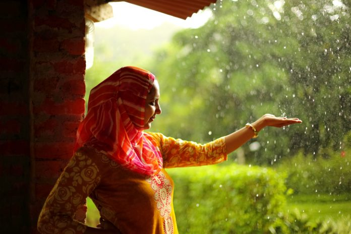 Muslim woman in traditional wear stretching her hand against the rain - travelling to Pakistan