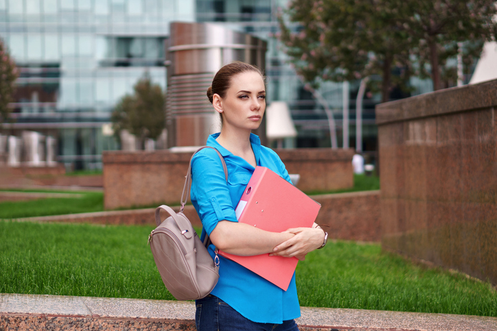 Woman carrying a Stylish backpack and file - Women's professional travel clothing