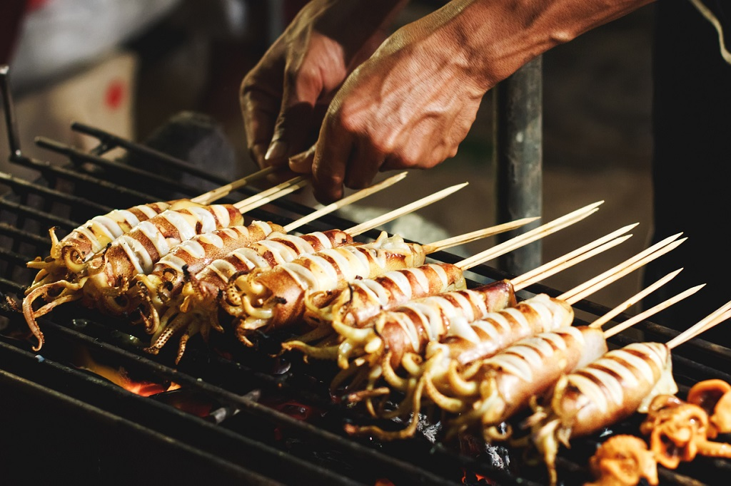 Street food preparing outdoors in Asian country, grilled bbq squids on sticks