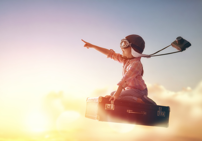 Child flying on a suitcase against the backdrop of a sunset